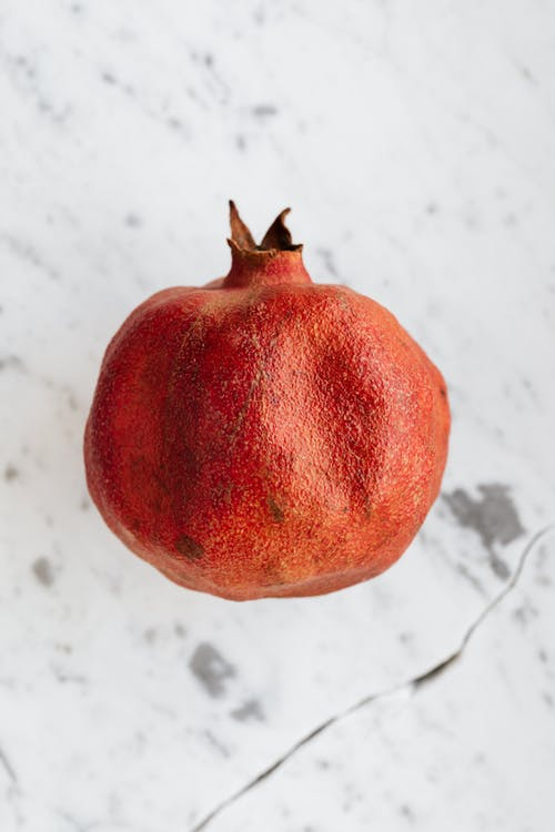 From above of whole ripe pomegranate with rough peel and small spiky leaves on top on marble surface with crack and grey spots