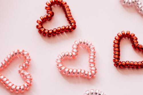 Colorful hair ties in shape of hearts on pink surface
