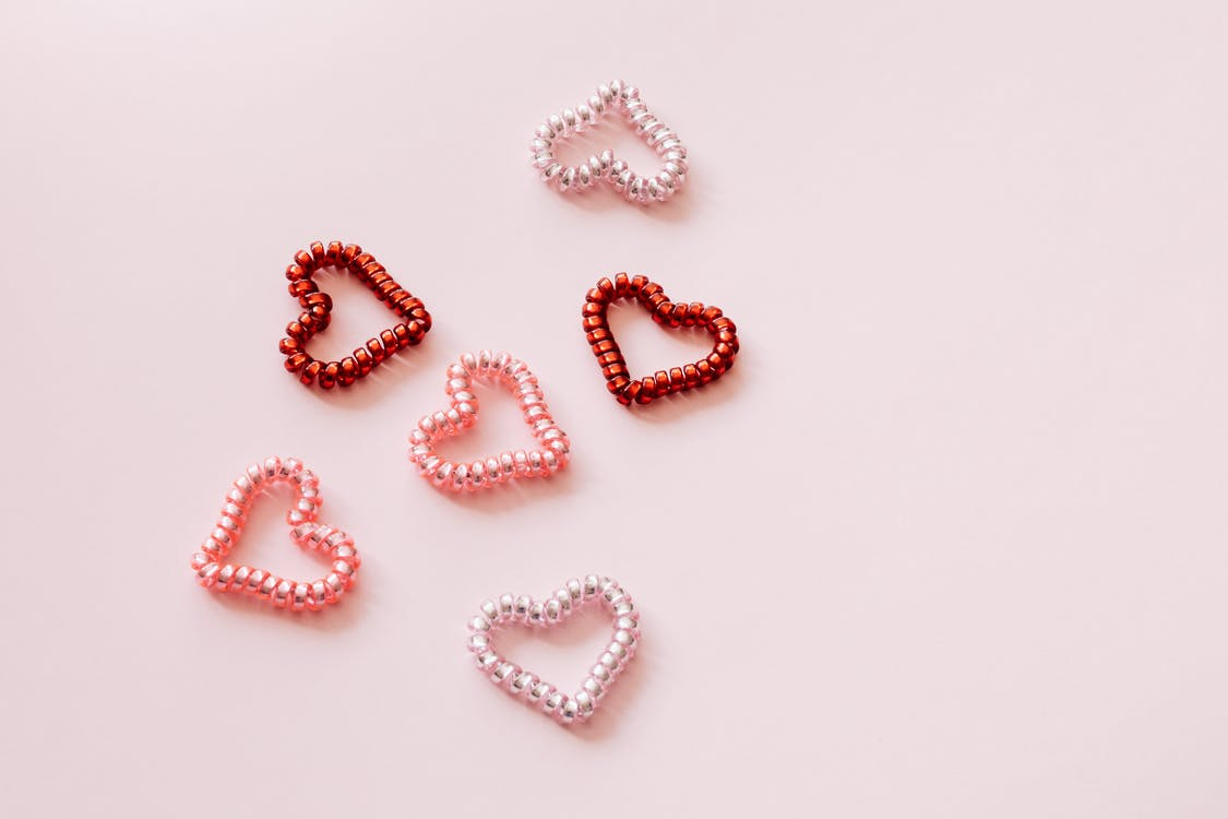Top view of composition of small multicolored decorative hearts made of shiny pearl globules on pale pink surface