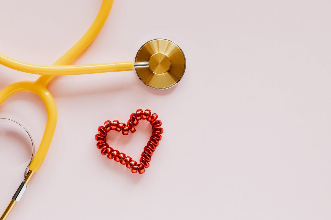 Plastic stethoscope with coil heart on pink background