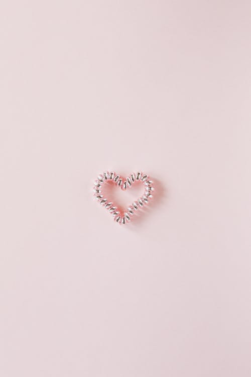 Decorative heart of elastic coil on pink background