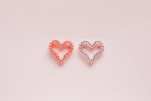 Decorative handmade bead hearts on pink background