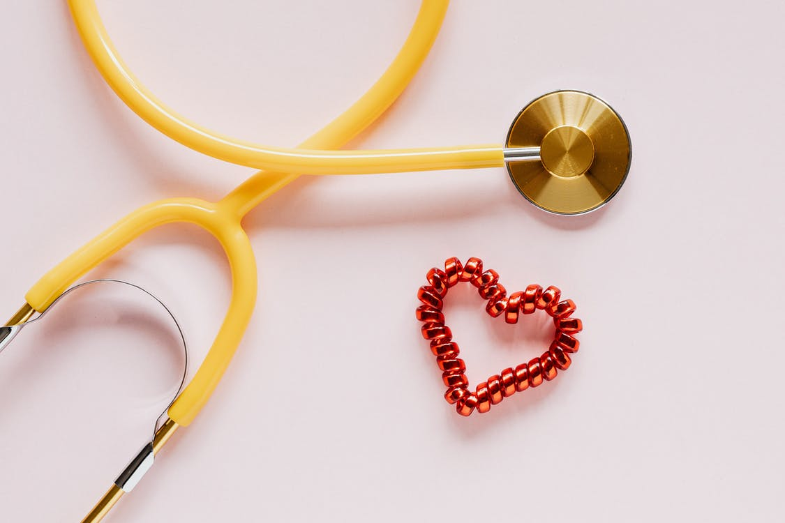 Stethoscope near decorative coil tie in heart shape on pink surface