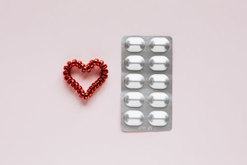 Top view of plastic blister with medical pills placed near red heart made of spiral elastic for hair on pink background