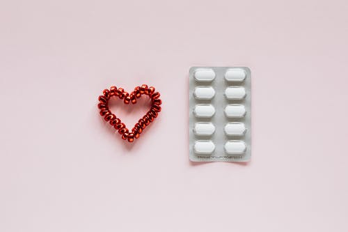 Composition of heart and pills on pink background