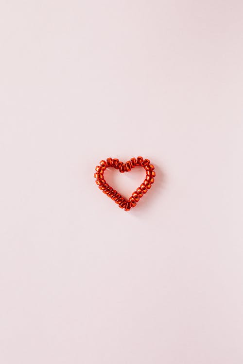 Red heart made of coil hair tie on pink background