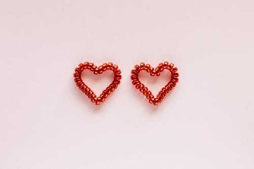 Top view creative composition of red spiral elastic in heart shaped placed on pink background