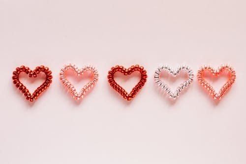 Composition of multicolored hearts on pink surface