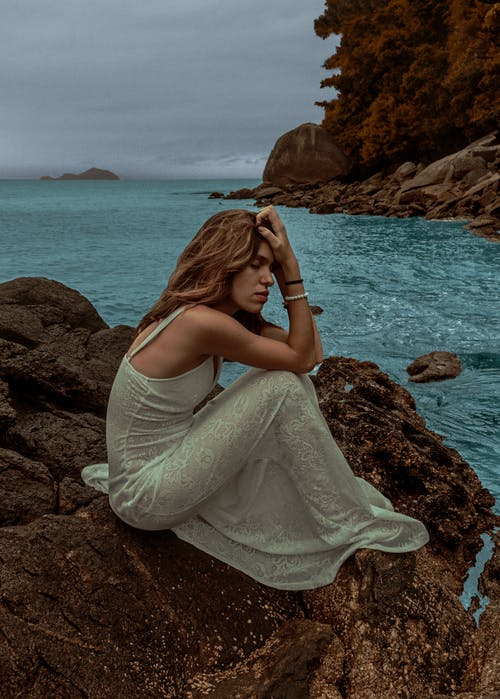 Young sad woman sitting on rocky shore