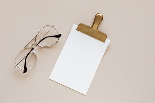 Composition of glasses and clip on beige background