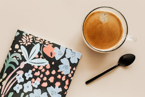 Cup of coffee and colorful diary on table