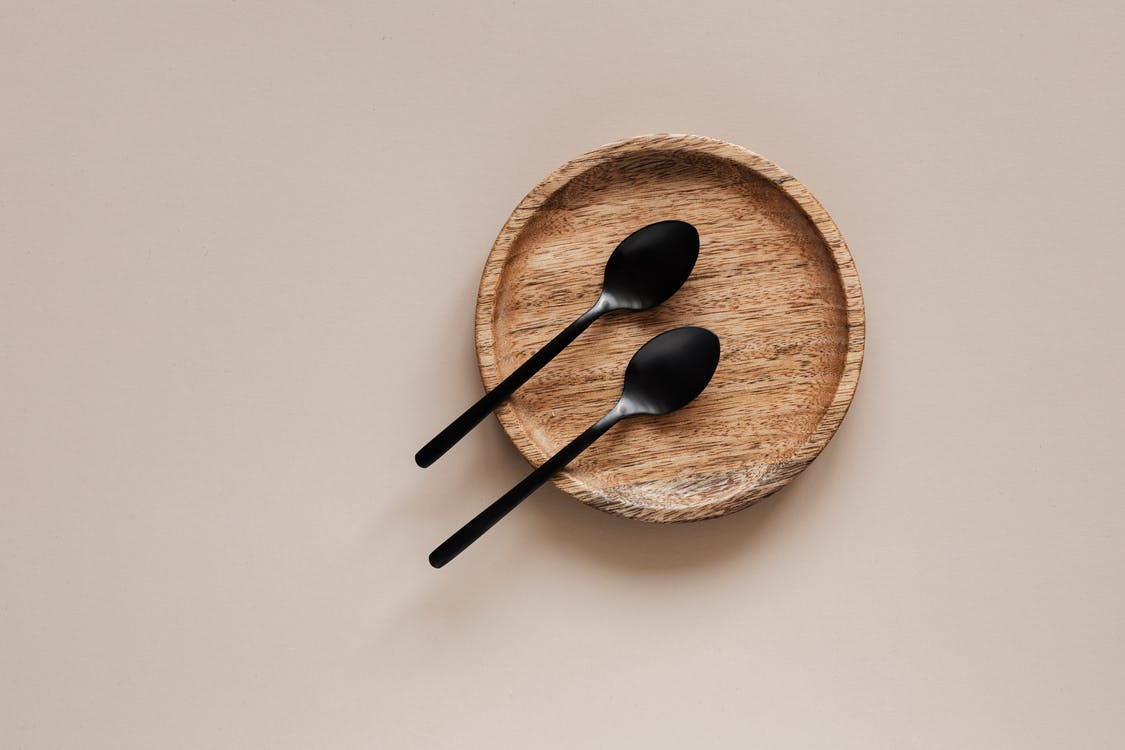 Top view of composition of round wooden plate with smooth surface and similar black metal spoons on beige surface