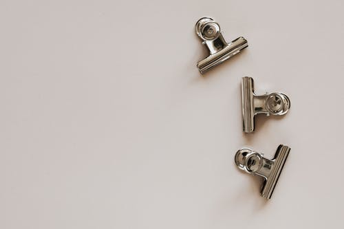 Set of metal clips on light grey background