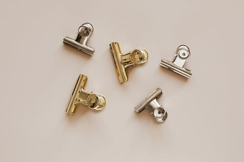 Set of metal clips on beige background