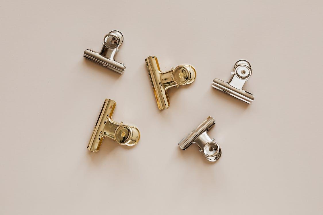 Set of metal clips on beige background