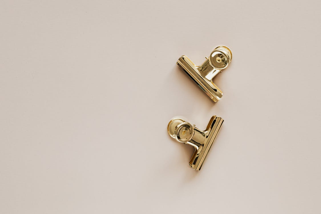 Golden metal clips on beige background