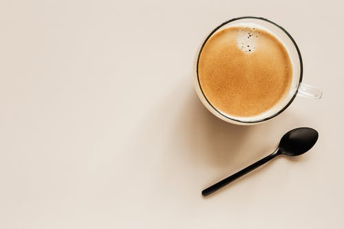 Top view of glass of aromatic light brown coffee with foam and small bubbles on top near metal spoon on beige surface
