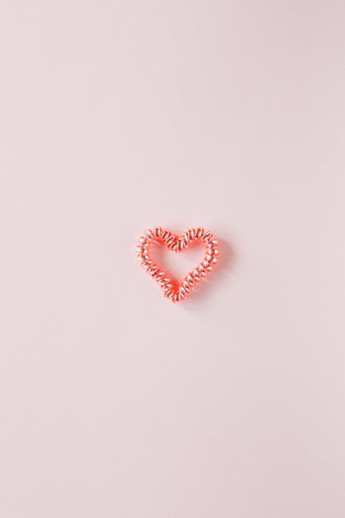 Small decorative heart on smooth pink surface