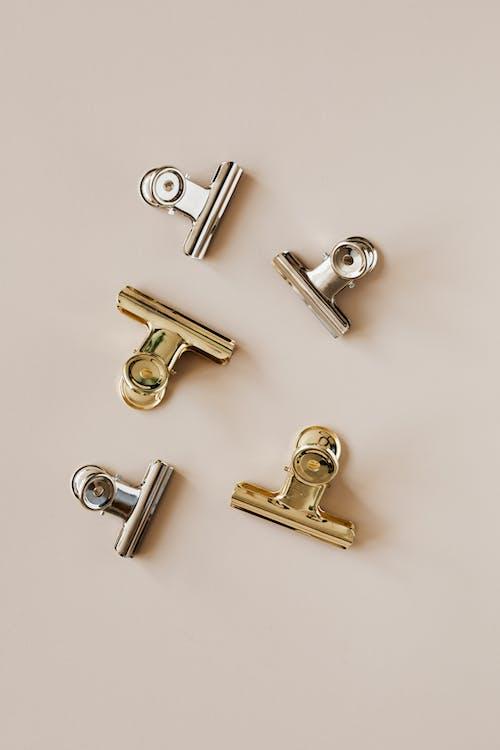 Kit of various metallic clips on beige surface