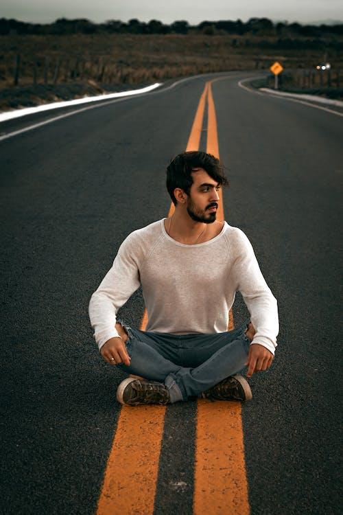 Dreamy ethnic man sitting on asphalt road