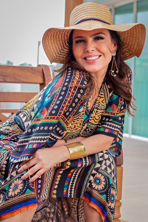 Cheerful female in colorful summer outfit and hat enjoying free time on bench