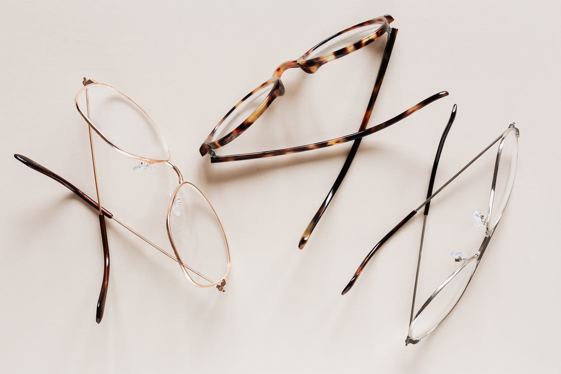 From above of fashion glasses with optical lenses for vision correction in metal shells together with pair in plastic tortoise shell placed on white table