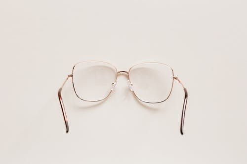 Top view of fashion spectacles with transparent optical lenses in golden metal shell placed on white table