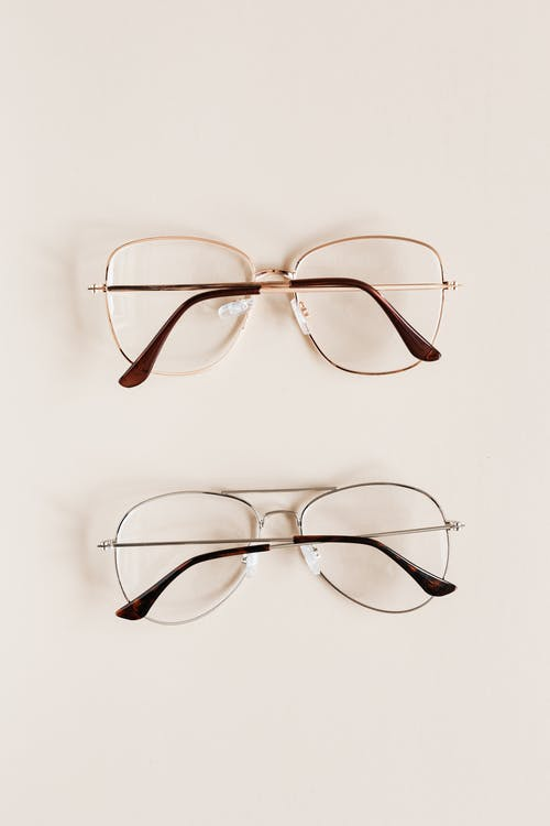 Stylish diverse glasses on beige background