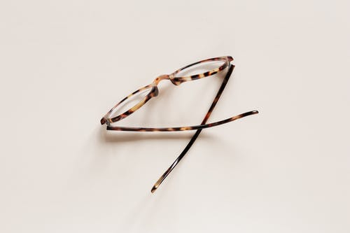 Stylish eyeglasses placed on beige surface