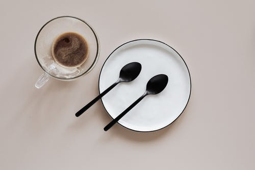 From above composition of ceramic plate with black spoons placed near glass cup of coffee on beige table