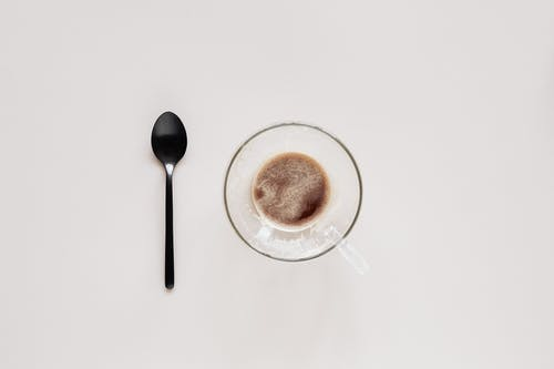 Cup of coffee and teaspoon on beige background