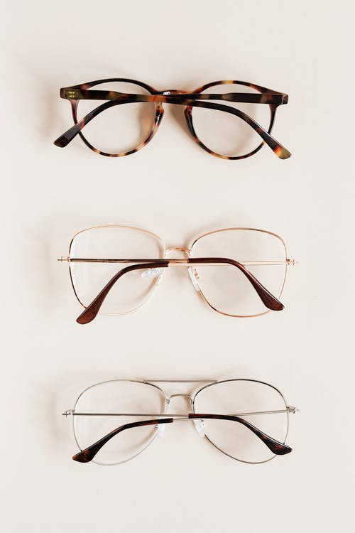 Stylish diverse glasses arranged in row lying down glasses on beige table
