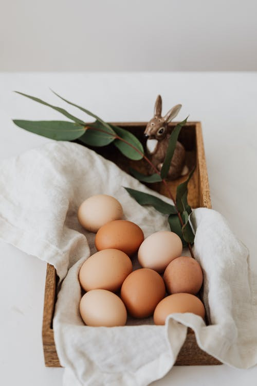 Brown Eggs and Ceramic Bunny on a Wooden Tray
