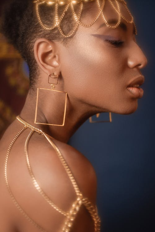 Young black calm woman with stylish golden accessories
