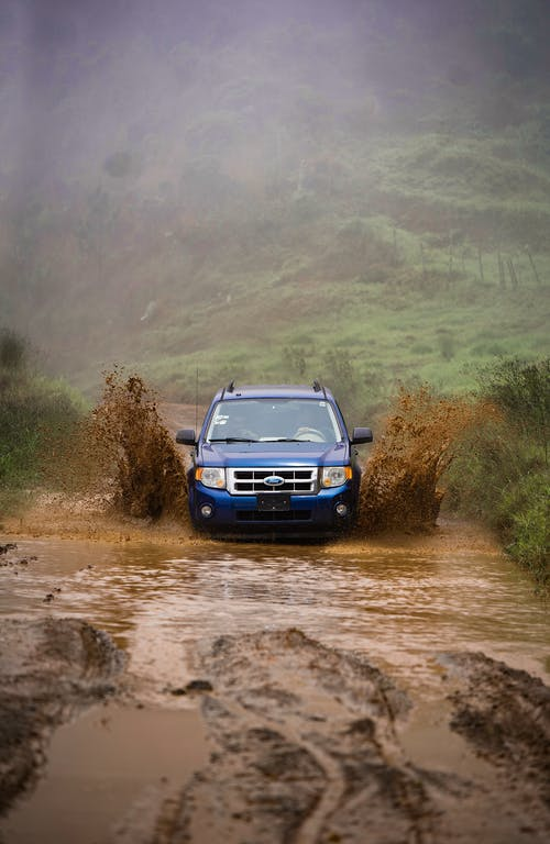 Blue Vehicle on Dirt Road
