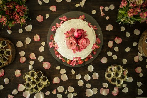 From above of delicious sweet cake decorated with roses and fresh strawberries placed near sweets on table with gentle petals of flowers