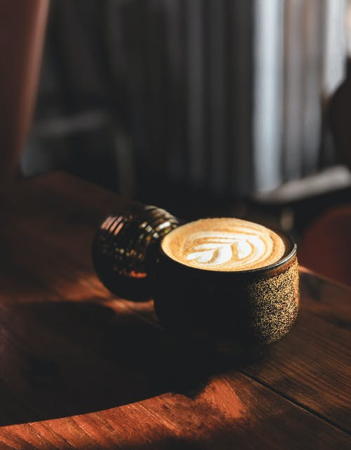 From above of mug of hot aromatic cappuccino placed on lumber table at sunlight
