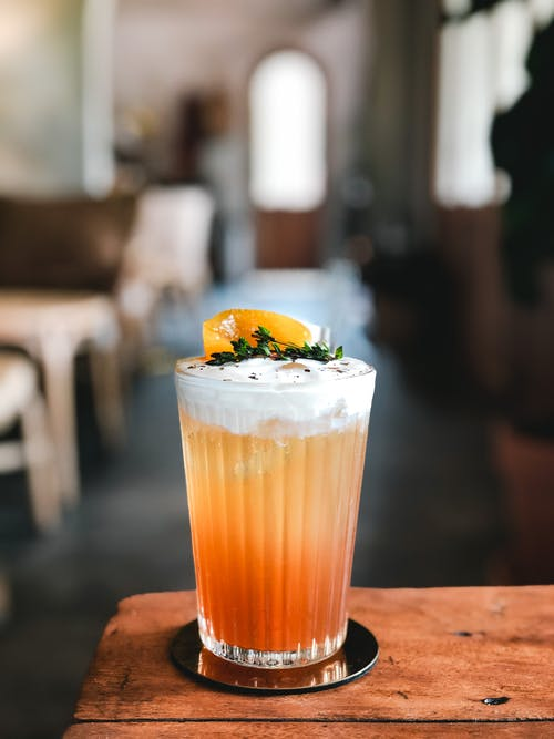 Transparent crystal glass of orange cocktail with white foam and fruit on top