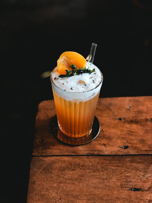 High angle of bright orange beverage decorated with fresh orange and mint placed on wooden table