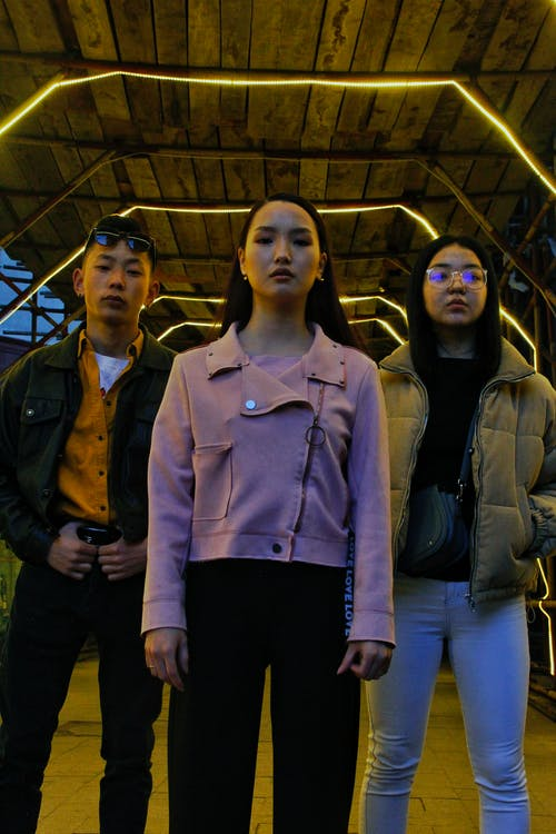 From below of young Asian friends in stylish clothes standing on street under roof with bright illumination