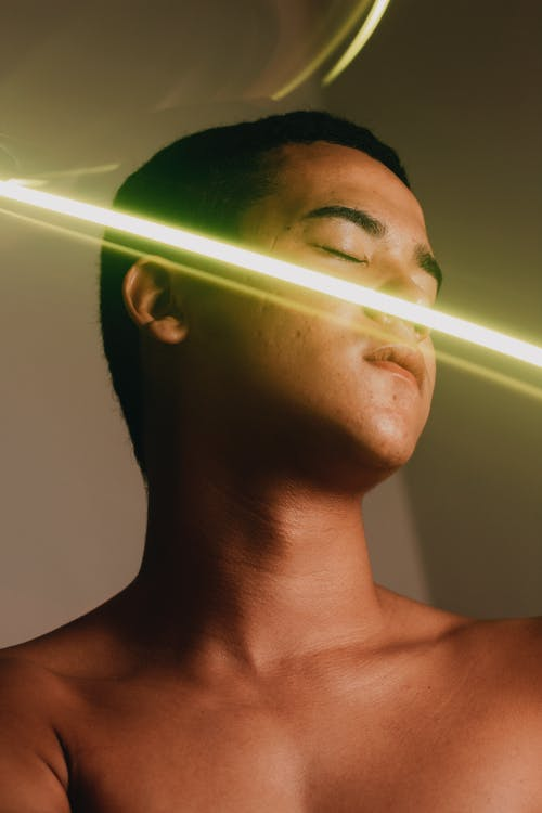 Shirtless man with closed eyes and freeze light