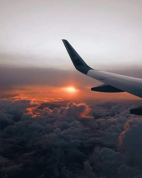 Wing of aircraft flying over cloudy sky and bright sun shining on horizon