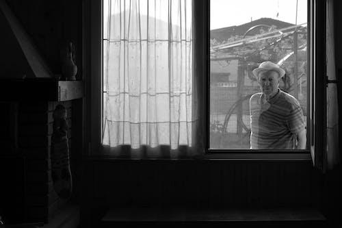 Grayscale Photo of Woman Standing Near Window
