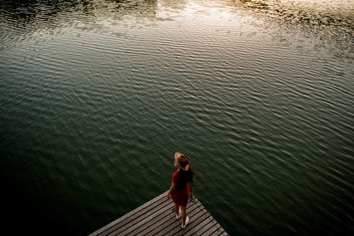 From above of anonymous female traveler in stylish dress and hat standing on wooden pier against rippling lake and admiring nature at sunset