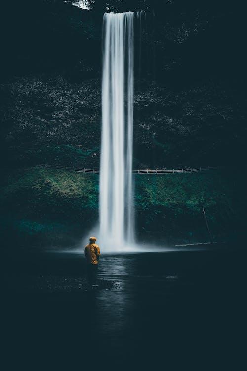 Anonymous tourist enjoying waterfall streaming in rocky ravine