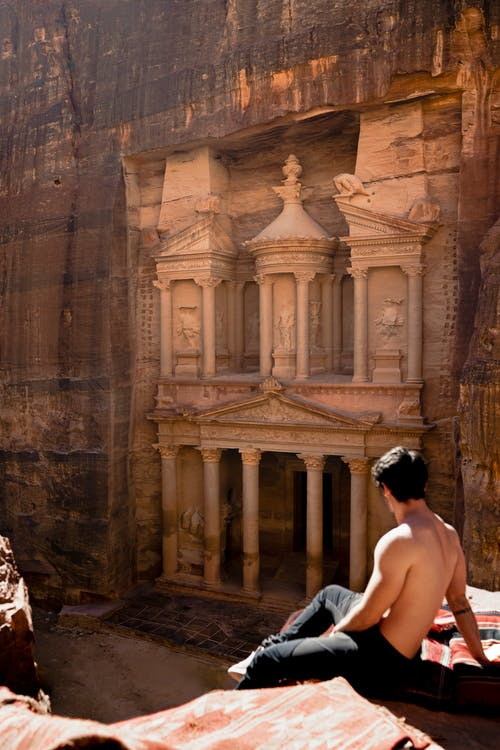 Topless Man Sitting on a Cliff Across the Famous Petra