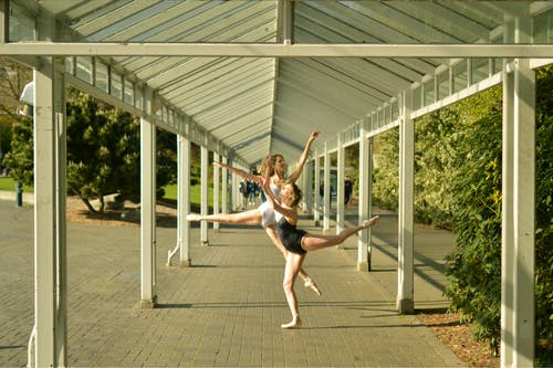 Flexible ballerinas performing dance on roofed pavement