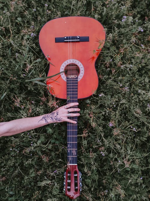 Crop tattooed musician with acoustic guitar on grass