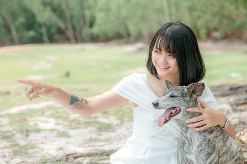 Ethnic woman hugging dog in park in daytime