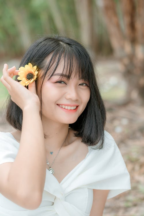 Happy Asian lady with bright flower in park
